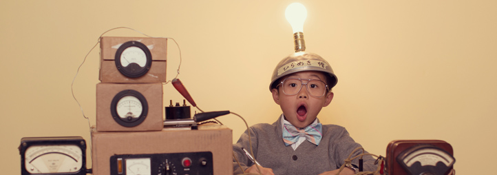 Kid sitting at a desk with light bulb hat