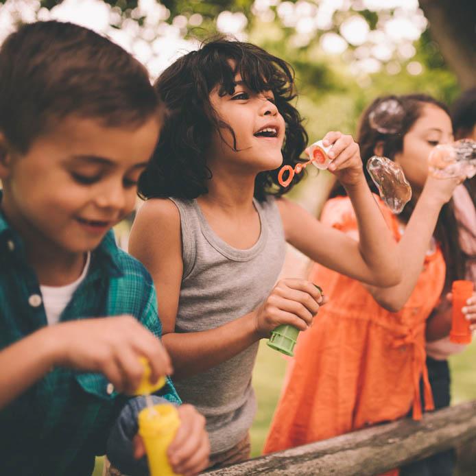 Groupe d'enfants arrêté sur une clôture de bois entrain de souffler des bulles