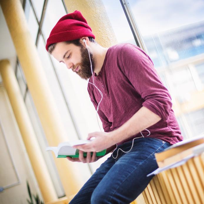 Étudiant caucasien avec une tuque rouge en train de lire près de la fenêtre