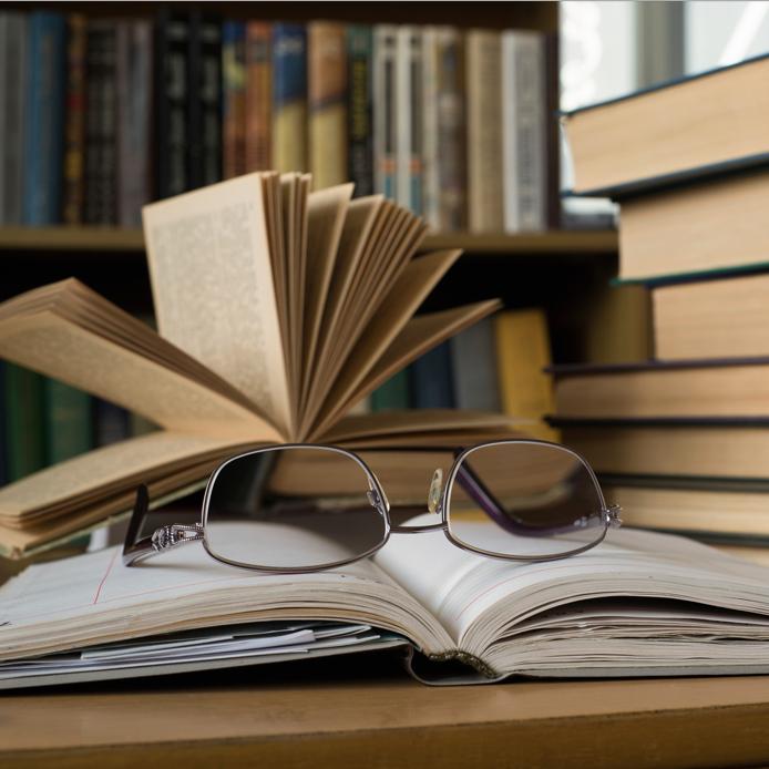Pile de livre sur le côté, et lunette sur un livre ouvert au centre