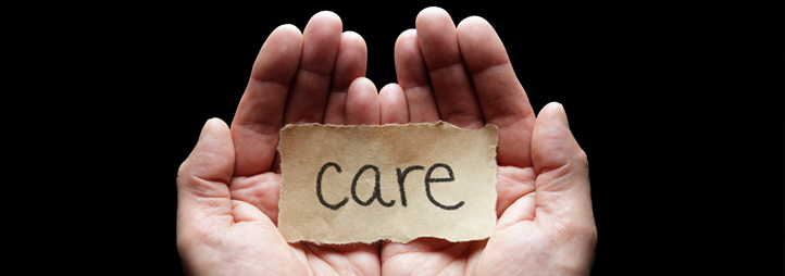 The word «Care» on a piece of brown paper, in someone's palm