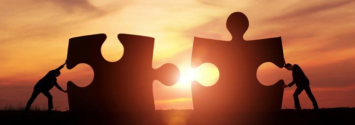deux hommes poussant deux pièces de casse-tête géantes ensemble devant le coucher du soleil