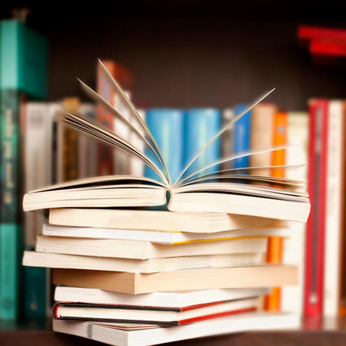 Pile de livres avec un ouvert sur le dessus. Il est situé sur une étagère de bibliothèque.