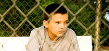 garçon derrière une clôture