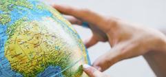 une main qui pointe à un endroit sur un globe