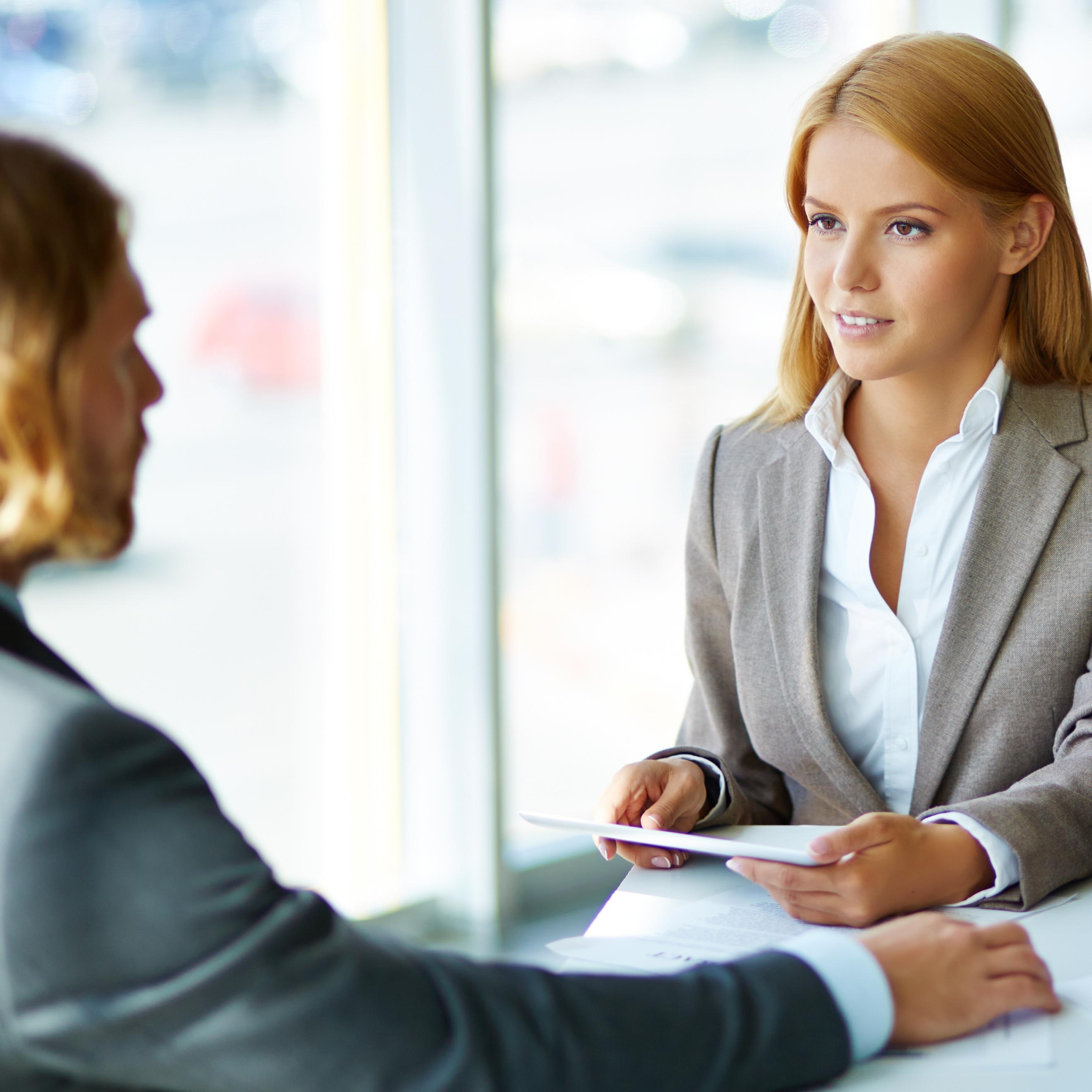 Deux hommes et une femme assisent à une table en discutant