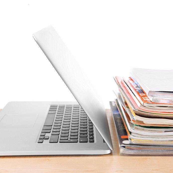 ordinateur portable partiellement ouvert avec une pile de publications à côté