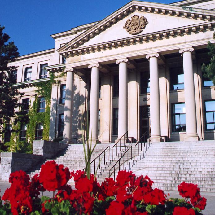 Entrée principale du bâtiment Tabaret en été avec des fleurs rouges