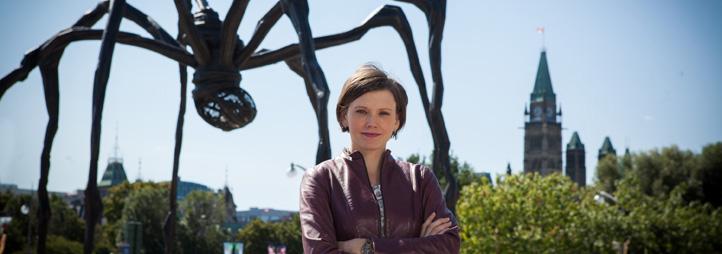 """Andrea Ashbaugh en avant de """"Maman"""" une grande sculpture d'araignée noire et les édifices du Parlement en arrière-plan"""