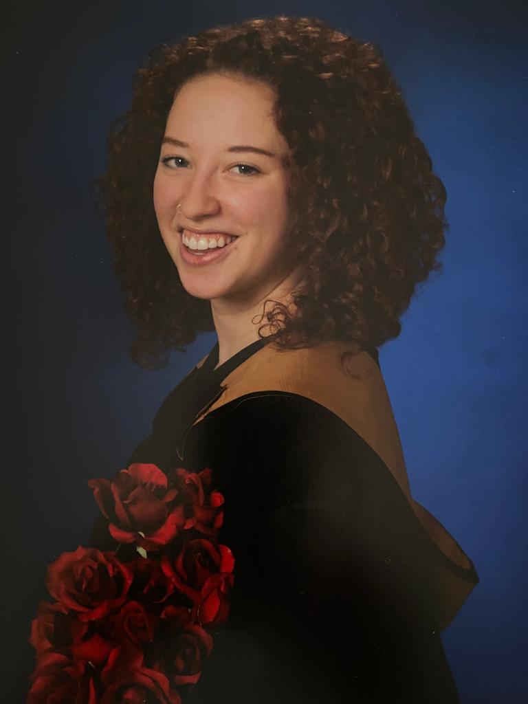 Janine's graduation photo. She is smiling toward the camera and holding a bouquet of red roses