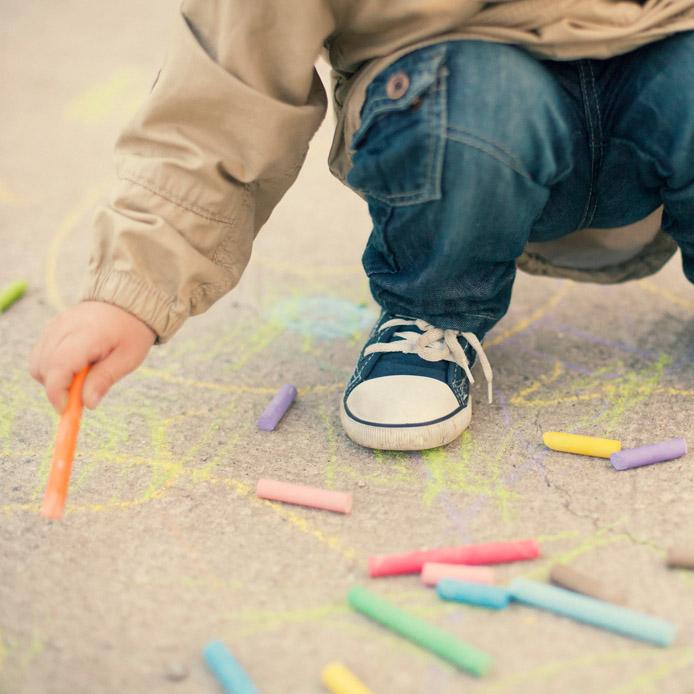 Enfant qui dessine avec de la craie