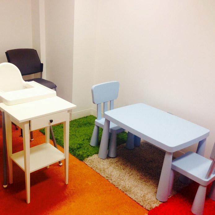 Salle avec une table et deux chaise d'enfant bleue, une chaise noir, une chaise haute blanche et du tapis coloré.