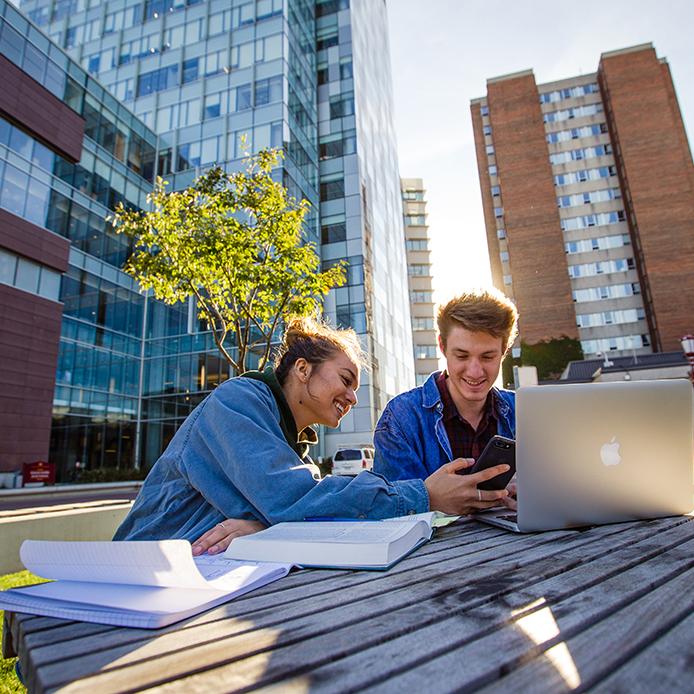deux étudiants regardant un smartphone tout en étudiant à l'extérieur devant le Pavillon des Sciences sociales