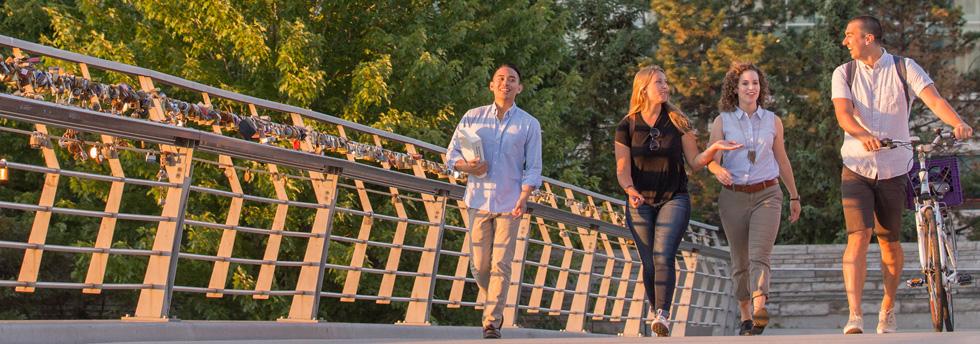 4 étudiants marchent sur un pont