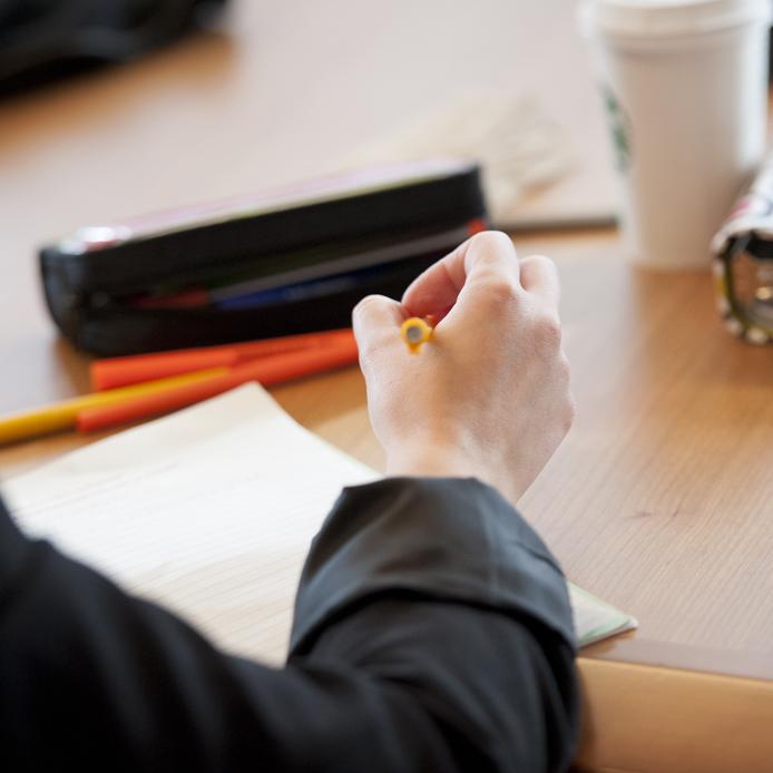 Une personne qui écrit sur un papier avec un crayon