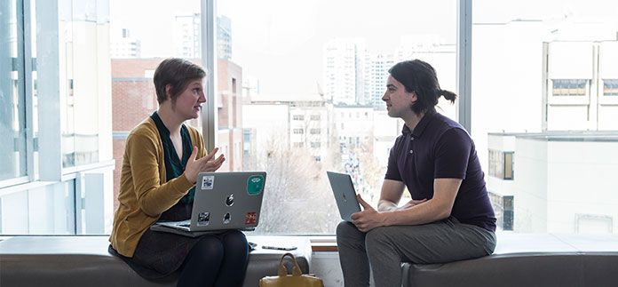 Two students with laptops discuss on two separate benches