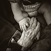 Baby and old person holding hands