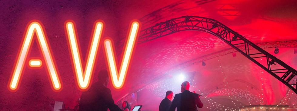 Logo de la Semaine des diplomés avec le A et W en neon et deux personnes en arrière plan.