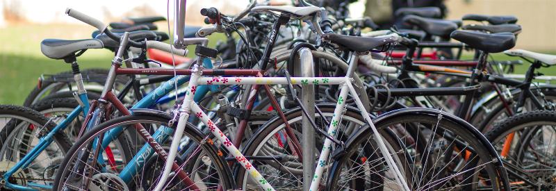 lots of bicycles locked up at a bike rack