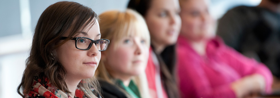 étudiants diplômés écoutant le professeur en classe