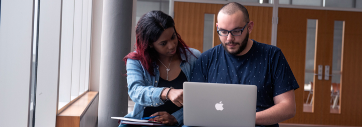Two young students working together on a laptop