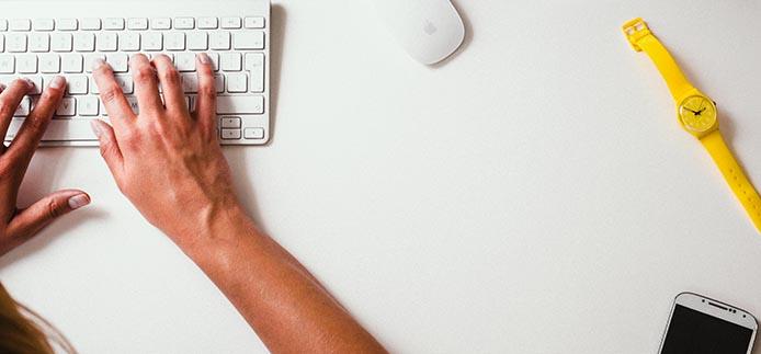 Deux mains tapant sur le clavier. Montre, souris et iphone visible.