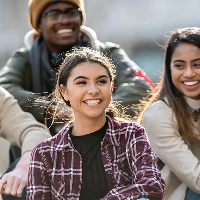 2 étudiantes et 1 étudiant de premier cycle souriant en plein air