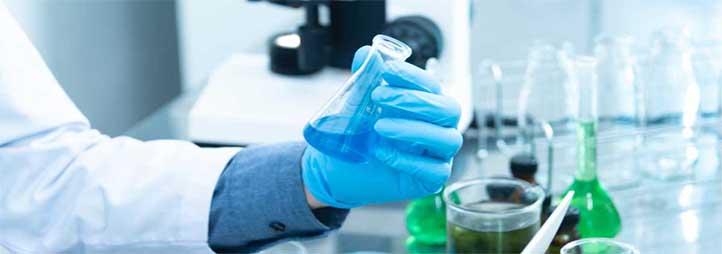 Image montrant les mains gantées d'un scientifique manipulant un tube à essai dans un laboratoire
