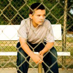 Garçon assis derrière une clôture