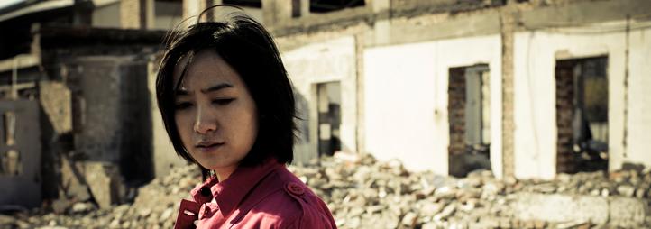 Femme devant édifice détruit