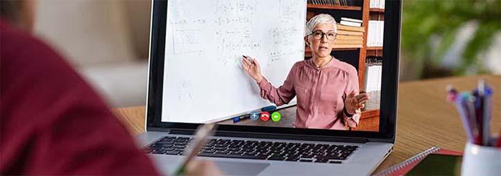 étudiant devant un écran, une professeure sur l'écran