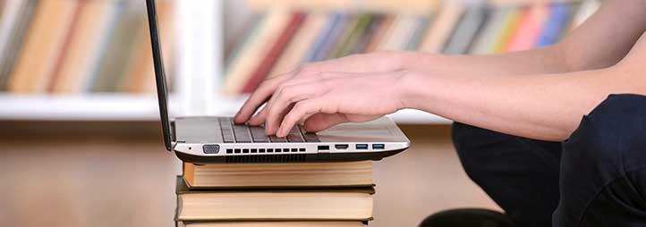 laptop sur une pile de livre et des mains qui tape