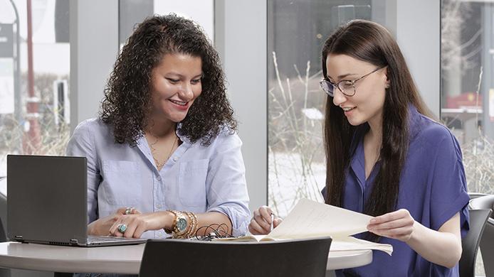 2 femmes étudient devant un ordinateur portable