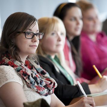 étudiantes diplômées écoutant le professeur en classe