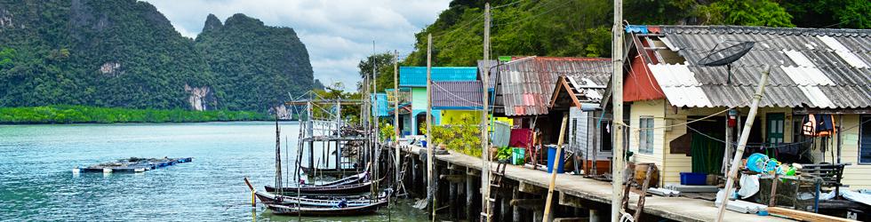 Maisons sur un quai le long d'une rivière en Thailande