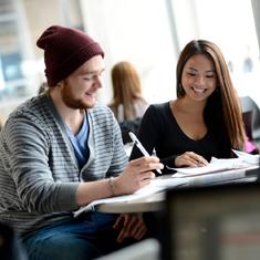 une étudiante et un étudiant du premnier cycle travaillant sur une table de cafétéria