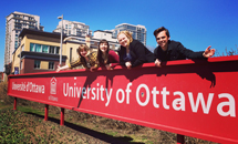 Students posing on uOttawa sign.