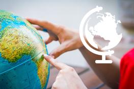 personne pointant pays sur un globe terrestre