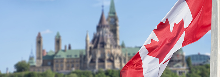 drapeau canadien avec les édifices du Parlement en arrière-plan