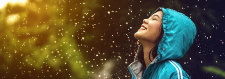 jeune femme en imperméable turquoise souriant sous l'averse
