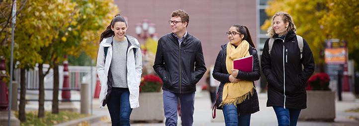 quatre étudiants qui marchent sur le campus