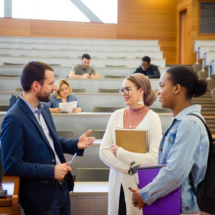 Professeur en discussion avec deux étudiantes de premier cycle en classe