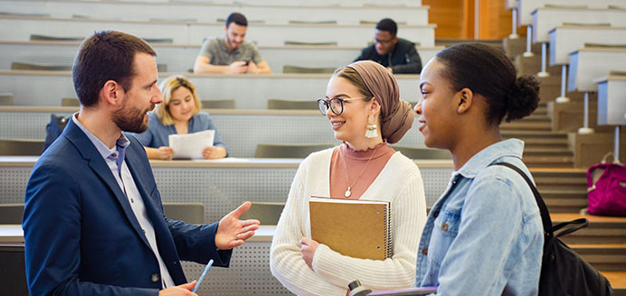 Two students chat with a professor