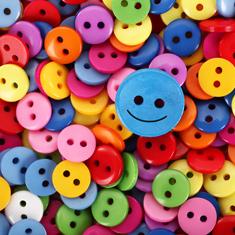 bouton avec visage heureux situé par-dessus d'autres boutons multicolores
