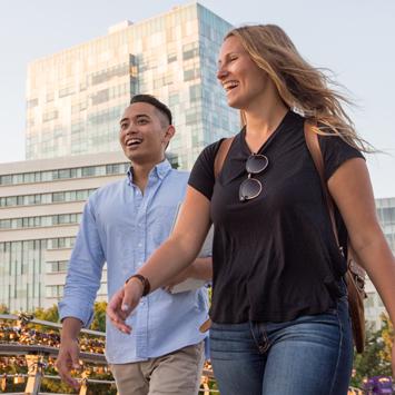 deux étudiants qui marchent à l'extérieur Pavillon des Sciences sociales derrière eux