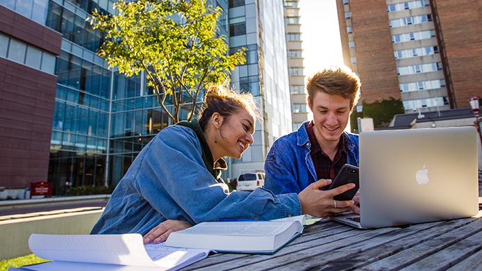 Une jeune femme et homme assis à l'extérieur de la FSS, étudiant