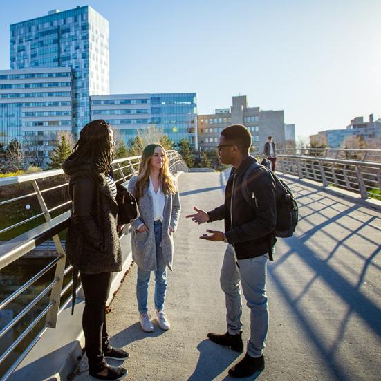 trois étudiants debout sur la passerelle devant le Pavillon des Sciences sociales